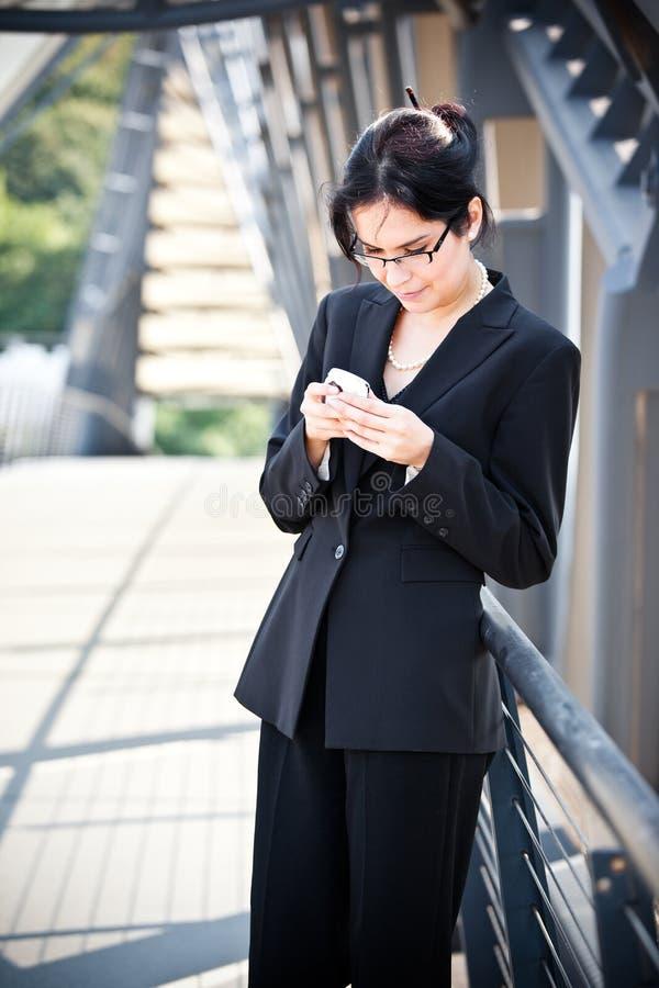 Hispanische texting Geschäftsfrau lizenzfreie stockbilder