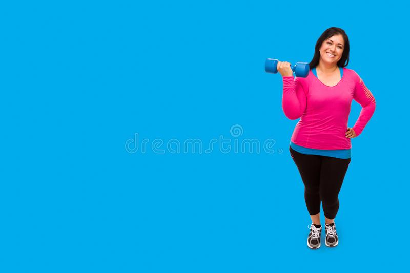 Hispanische vrouw in werkkleding die Dumbbell vasthoudt tegen een heldere cyaan blauwe achtergrond royalty-vrije stock afbeeldingen