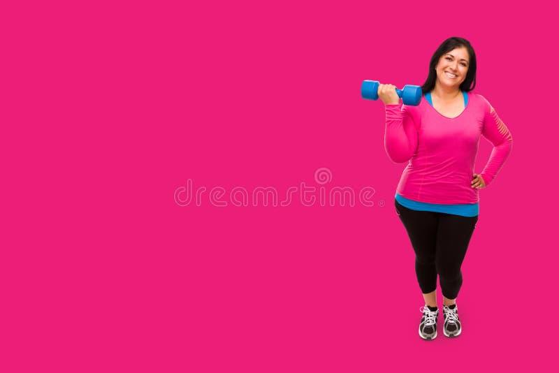 Hispanische vrouw in werkkleding die Dumbbell vasthoudt tegen een heldermagenta roze achtergrond royalty-vrije stock afbeeldingen