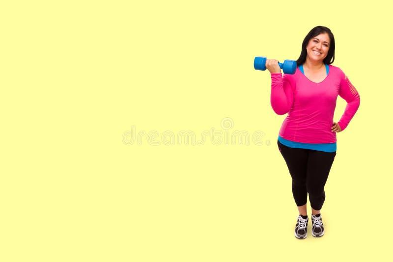 Hispanische vrouw in werkkleding die Dumbbell vasthoudt tegen een licht gele achtergrond stock fotografie