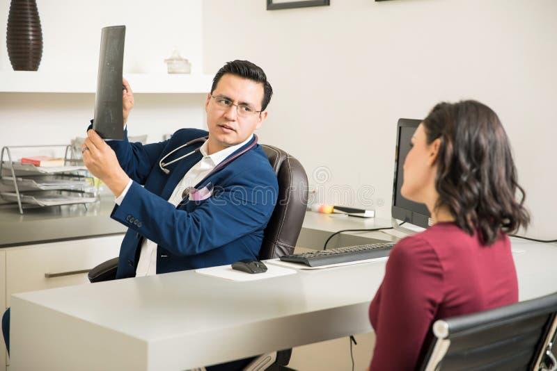 Hispanischer Doktor, der Röntgenstrahlen Patienten erklärt lizenzfreie stockfotografie