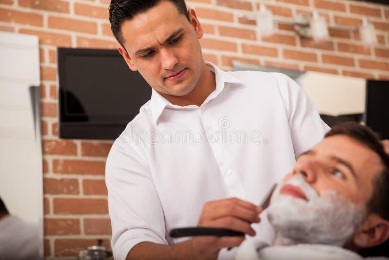 Hispanischer Friseur, der einen Mann rasiert stockfoto