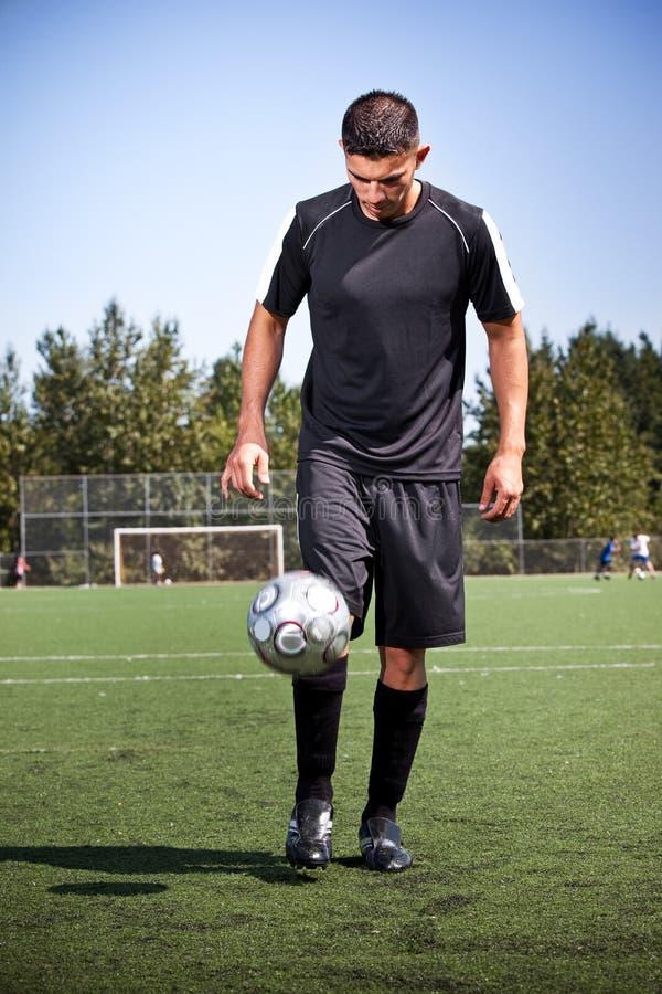 Hispanischer Fußball- oder Fußballspieler, der eine Kugel tritt stockbilder