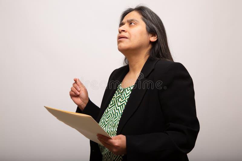Hispanischer Geschäftsfrau-Deeply Thinking While-Holding-Ordner lizenzfreies stockfoto