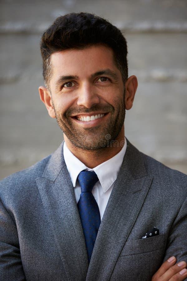 Hispanischer Geschäftsmann Standing Against Wall im modernen Büro stockbild