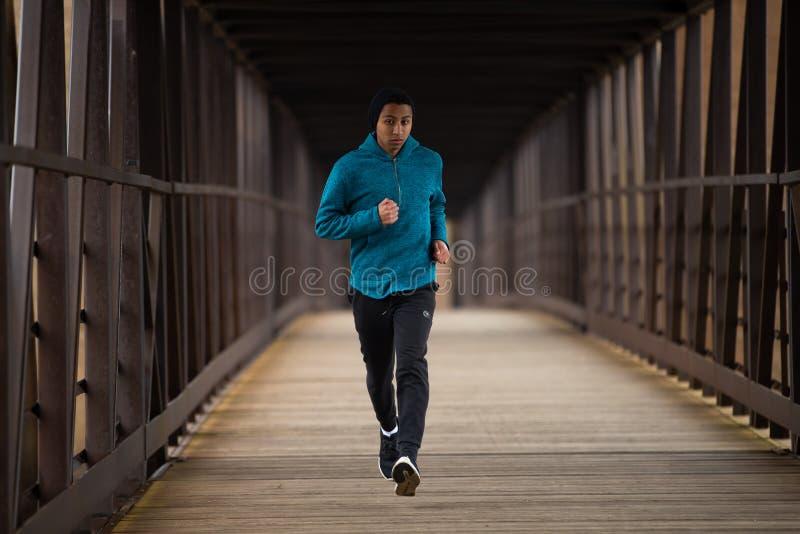 Hispanischer Jugendlicher, der allein an auf einer Brücke läuft stockfotografie