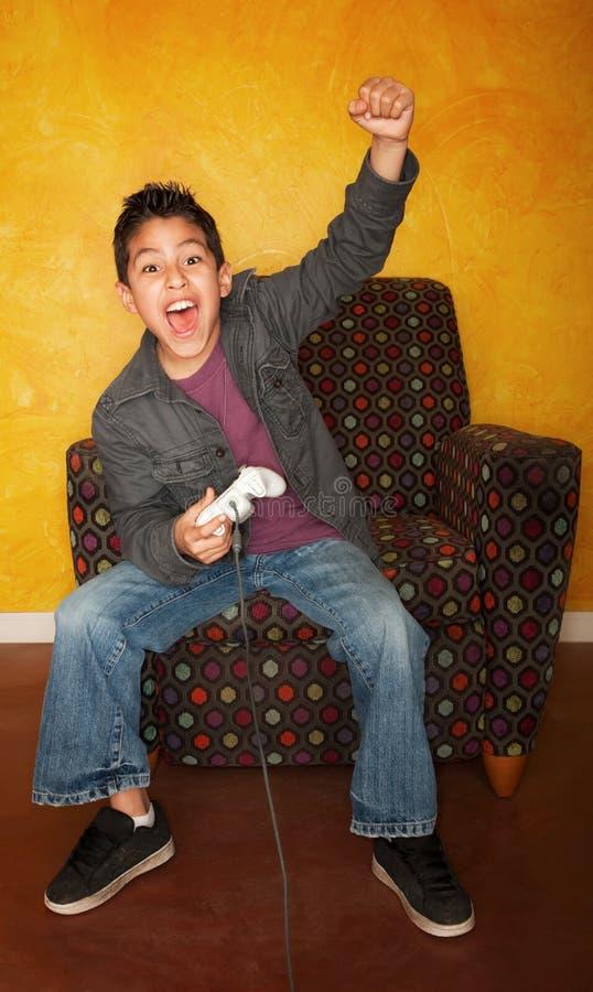 Hispanischer Junge, der Videospiel spielt lizenzfreie stockbilder