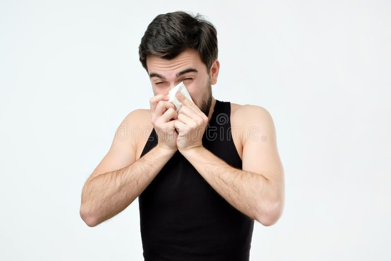Hispanischer junger Mann mit dem schwarzen Bart, der krankes Niesen ist stockbilder