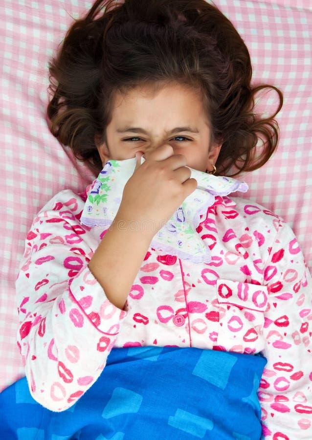 Hispanischer Mädchenkranker mit der Grippe, die in ihr Bett legt lizenzfreie stockbilder
