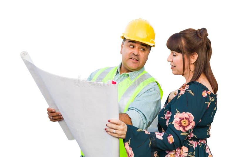 Hispanischer männlicher Auftragnehmer, der mit dem weiblichen Kunden über Plan-Plänen lokalisiert auf einem weißen Hintergrund sp lizenzfreie stockbilder