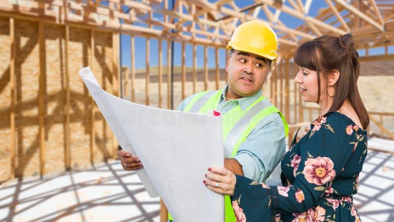 Hispanischer männlicher Auftragnehmer, der mit weiblichem Kunden über Plan-Plänen an der Baustelle spricht lizenzfreies stockfoto