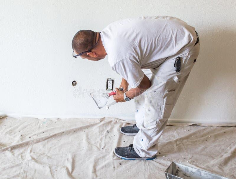 Hispanischer Maler, der Spackle auf eine Wand setzt lizenzfreies stockbild