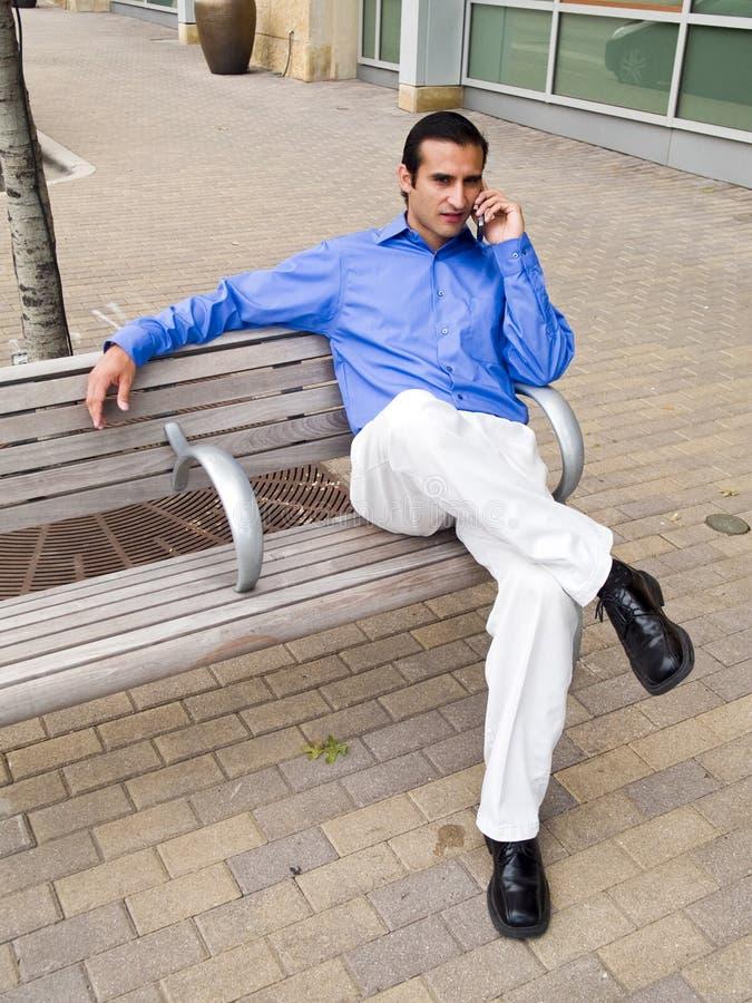 Hispanischer Mann auf Handy stockfoto