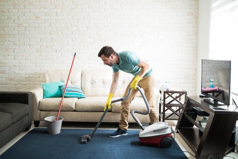 Hispanischer Mann, der das Wohnzimmer Staub saugt lizenzfreies stockbild