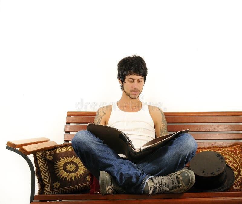 Hispanischer Mann, der eine Zeitschrift liest stockfoto