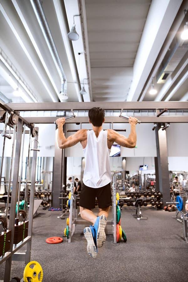 Hispanischer Mann in der Turnhalle, die ZugUPS auf horizontaler Stange tut stockbilder