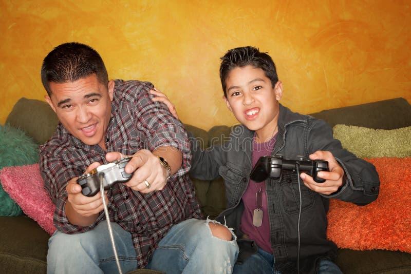 Hispanischer Mann und Junge, die Videospiel spielt lizenzfreies stockbild