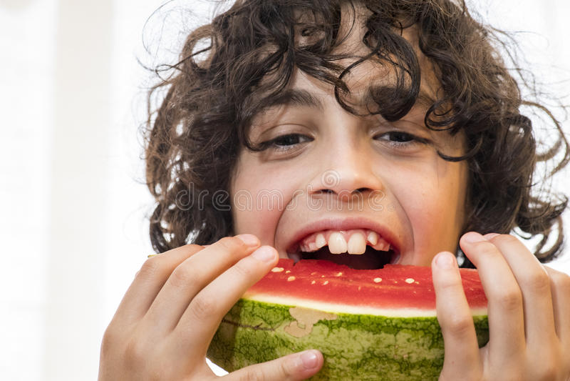 Hispanisches Kind, das neue Wassermelonenscheibe isst lizenzfreie stockfotografie