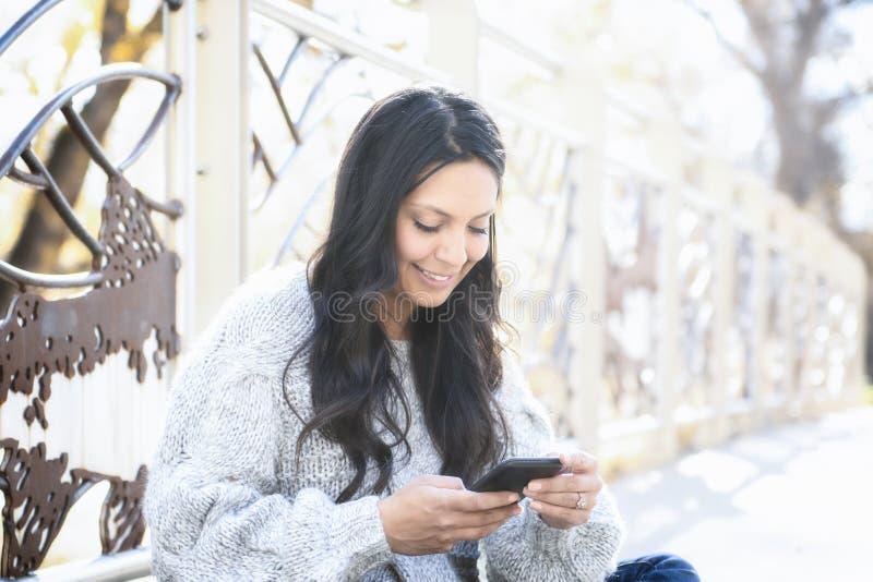 Hispanos jovenes hermosos, mujer india, multirracial americana con el teléfono celular fotos de archivo