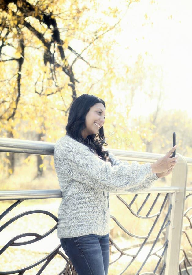 Hispanos jovenes hermosos, mujer india, multirracial americana con el teléfono celular imagenes de archivo
