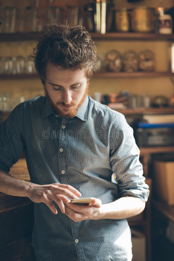 Hispter guy with mobile phone in the bar royalty free stock photography