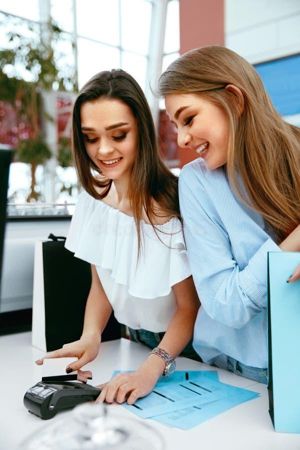 hissar, exponeringsglas och metall Flickor som betalar med kreditkorten royaltyfri fotografi
