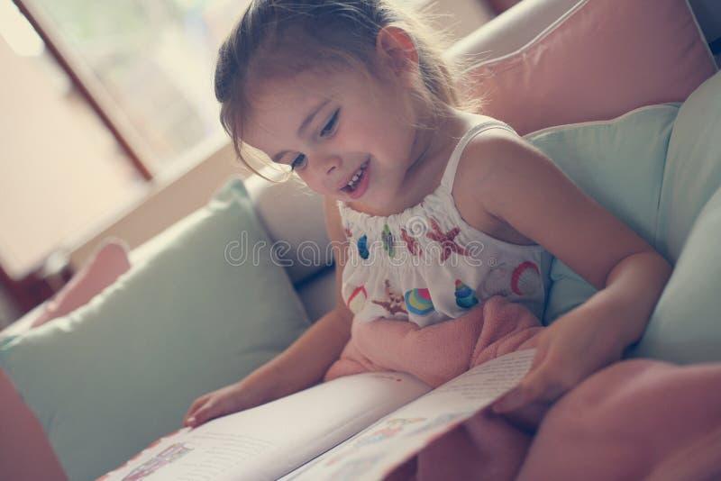 História da leitura da menina em casa imagens de stock royalty free
