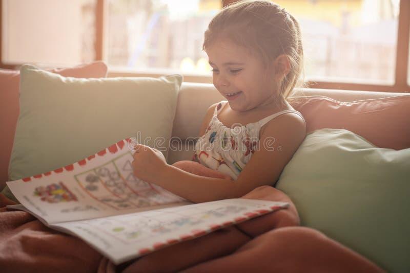 História da leitura da menina em casa foto de stock royalty free