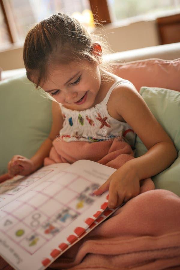 História da leitura da menina em casa imagens de stock