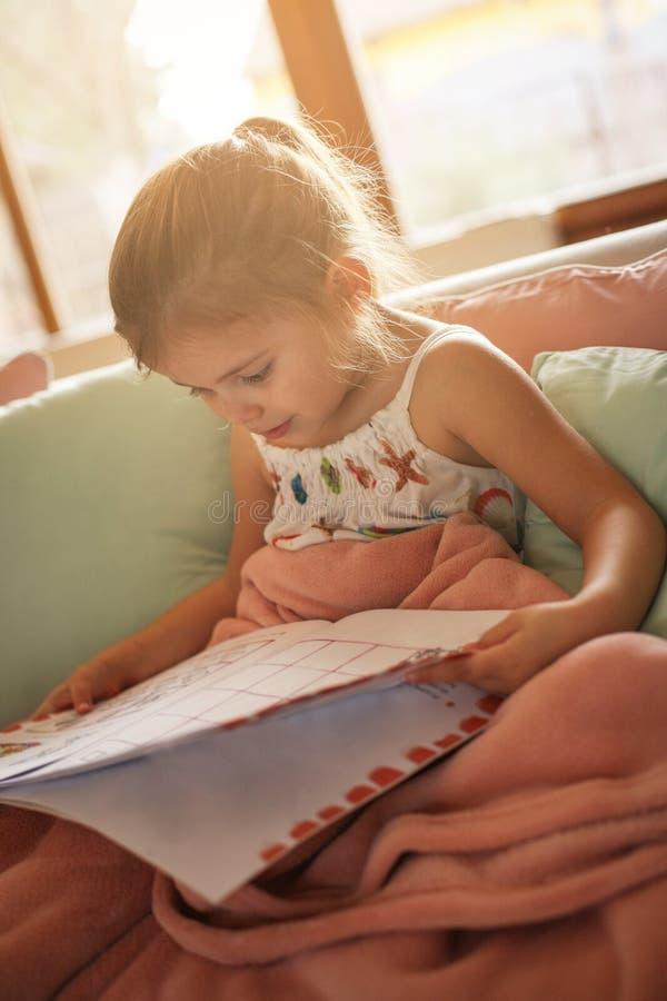 História da leitura da menina em casa fotografia de stock