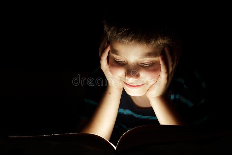 História de horas de dormir da leitura do menino imagens de stock