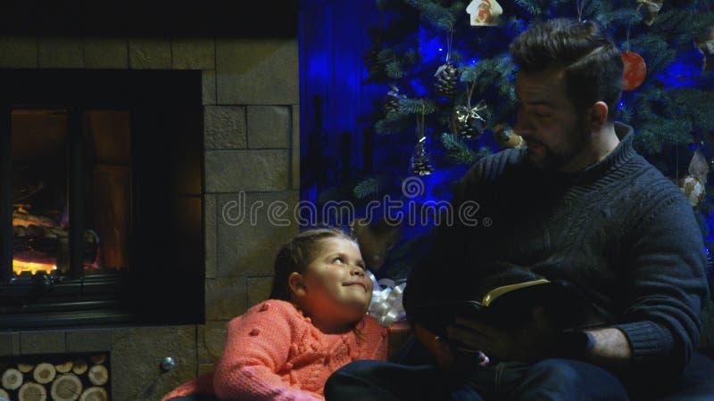 História do Natal da leitura do homem à filha imagem de stock royalty free