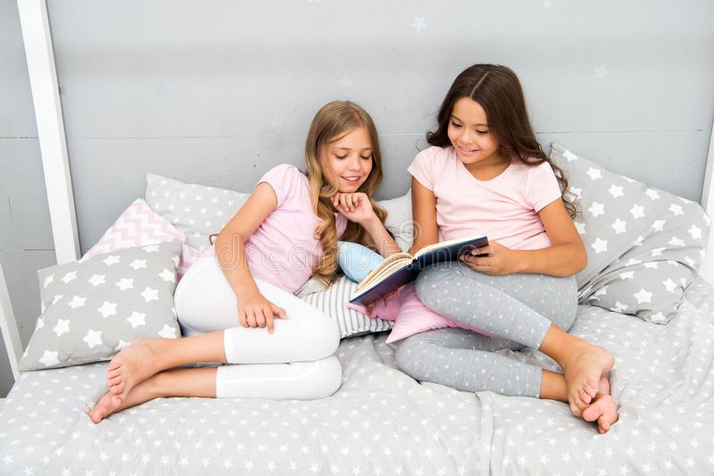 Histórias que cada criança deve ler As crianças leram o livro na cama Os melhores amigos das meninas leram o conto de fadas antes fotografia de stock royalty free