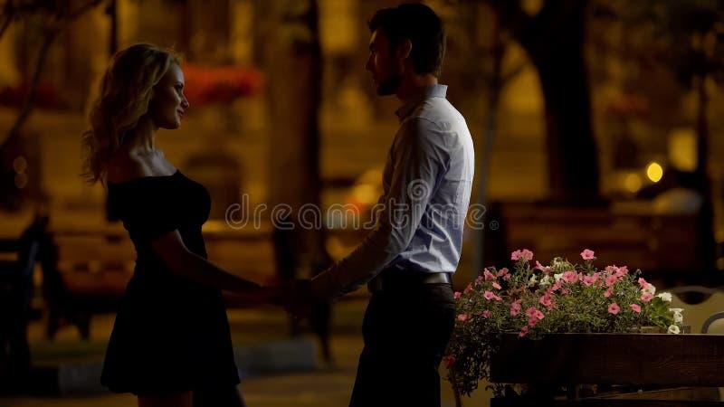 Histoire d'amour, couple aimant tenant des mains et regardant l'un l'autre, égalisant le temps photographie stock libre de droits