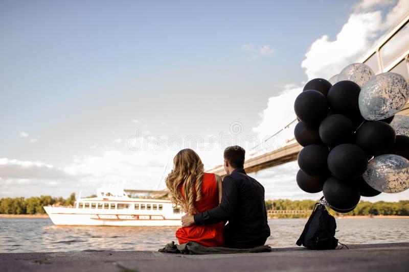 Histoire d'amour de jeunes couples sur le fond de la rivière images stock