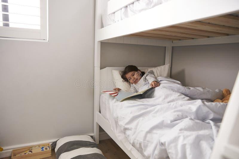 Histoire de lecture de fille dans le lit superposé à l'heure du coucher photographie stock libre de droits