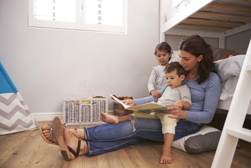 Histoire de lecture de mère aux enfants dans leur chambre à coucher images libres de droits