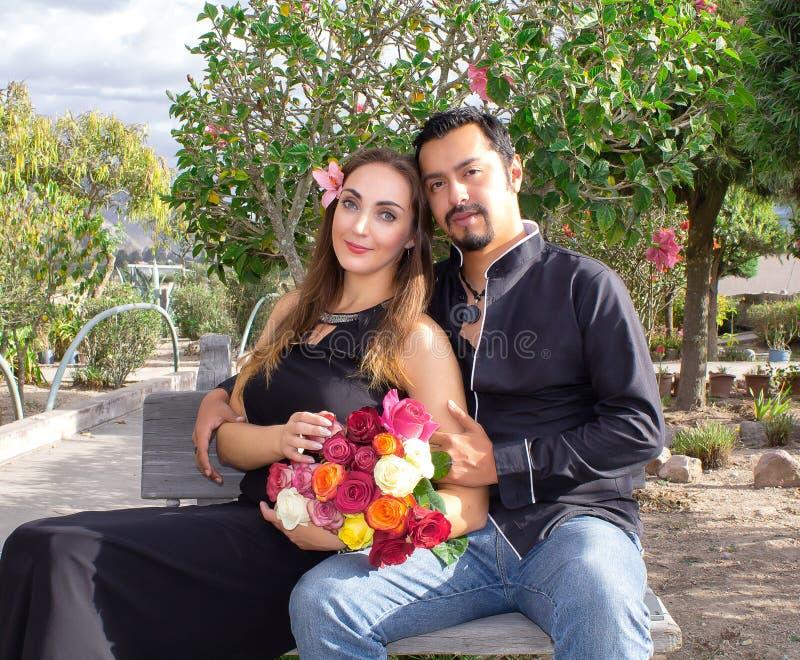 Historia de amor Un hombre y una mujer están abrazando sentarse en un banco en naturaleza en un jardín floreciente Con un ramo de imagen de archivo