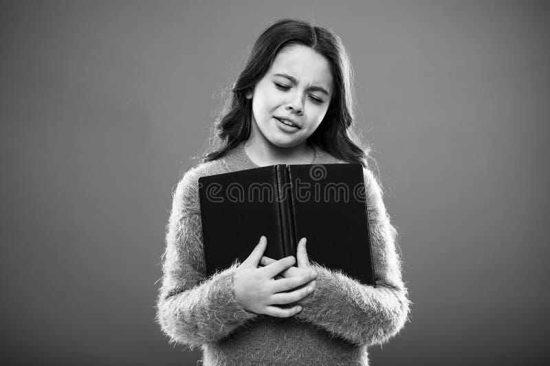 Historia de terminación triste El libro del control de la muchacha leyó historia sobre fondo anaranjado El niño goza del libro de imágenes de archivo libres de regalías