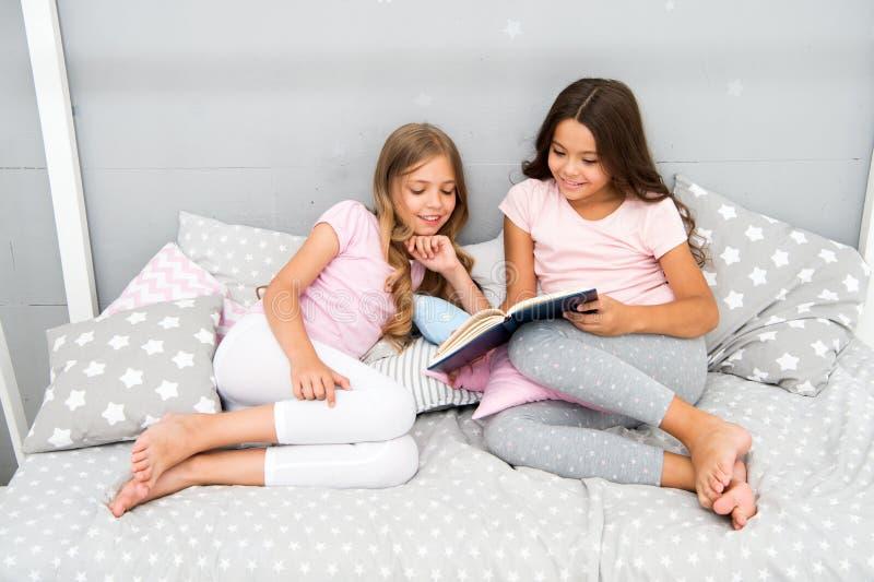 Historias que cada niño debe leer Los niños leyeron el libro en cama Los mejores amigos de las muchachas leyeron cuento de hadas  fotografía de archivo libre de regalías
