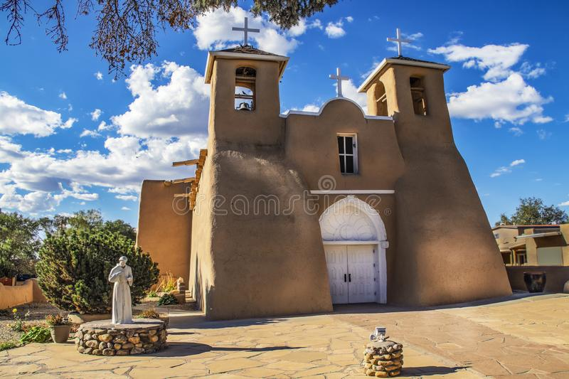 Historic adobe San Francisco de Asis Mission Church in Taos New Mexico in dramatic late afternoon light under intense blue sky wit royalty free stock image