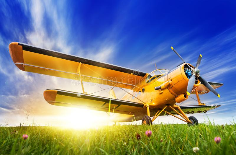 Historic biplane. On a meadow against a sunset royalty free stock photo