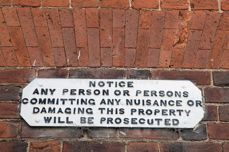 Historic black and white lettered warning sign. Historic black and white warning sign about prosecuting nuisance, the sign against a brick wall stock photography