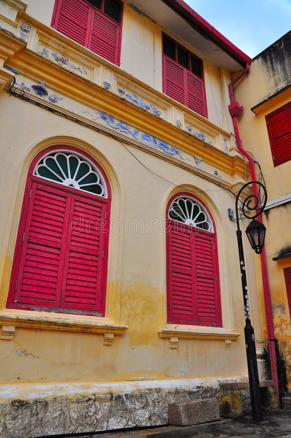 Historic building with red louvered windows. Historic building exterior with red louvered windows royalty free stock photo