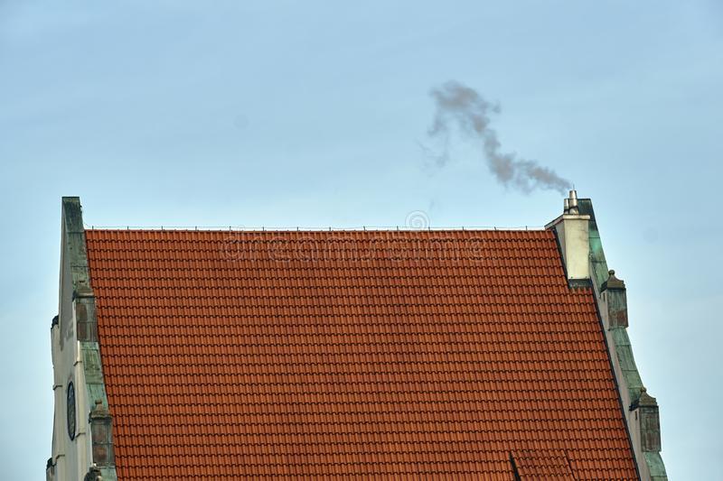 A historic building with a roof made of red tiles and a smoking chimney. In Poznan stock image