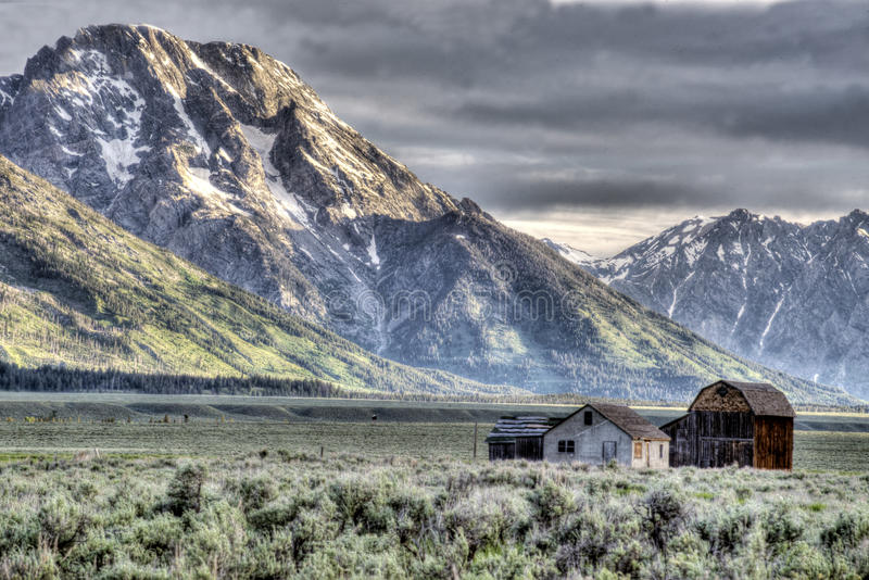 Historic buildings below snow capped mountains in The Grand Tetons. Snow capped mountains and valley in The Grand Tetons stock photography