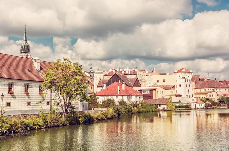 Historic buildings with reflections in water reservoir. Jindrichuv Hradec, Czech republic. Architectural scene. Travel destination. Yellow photo filter stock photo