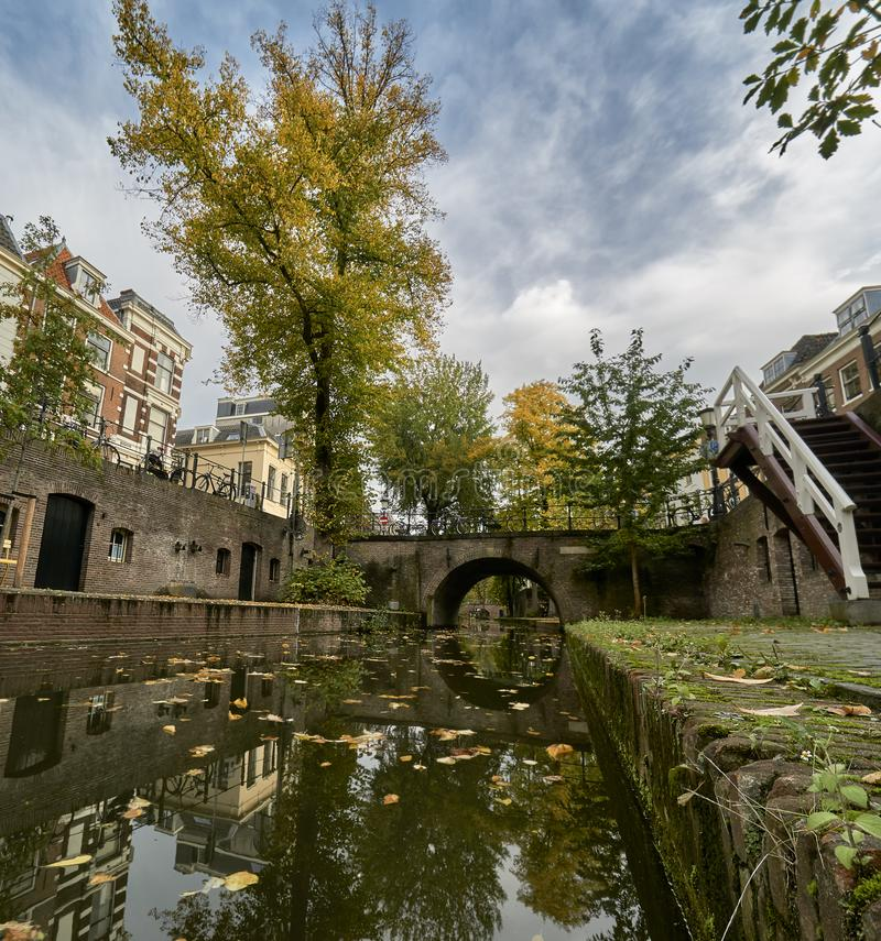 Historic canal in the city center of Utrecht in the netherlands during fall with leaves covering the ground stock photo