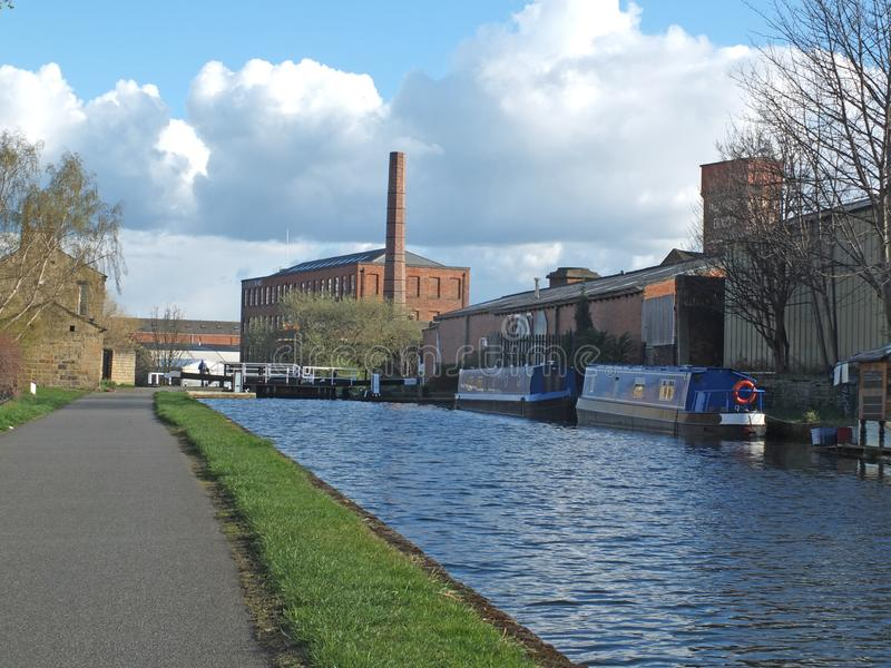 The historic castleton mill near armley in leeds and oddy lock gates and footbridge crossing the canal with moored houseboats. And towpath royalty free stock photo