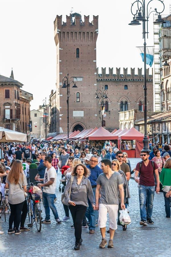 Historic center of the city of Ferrara in Italy. Many people walk in the street. FERRARA, ITALY. April 21, 2018: Historic center of the city of Ferrara in Italy royalty free stock image